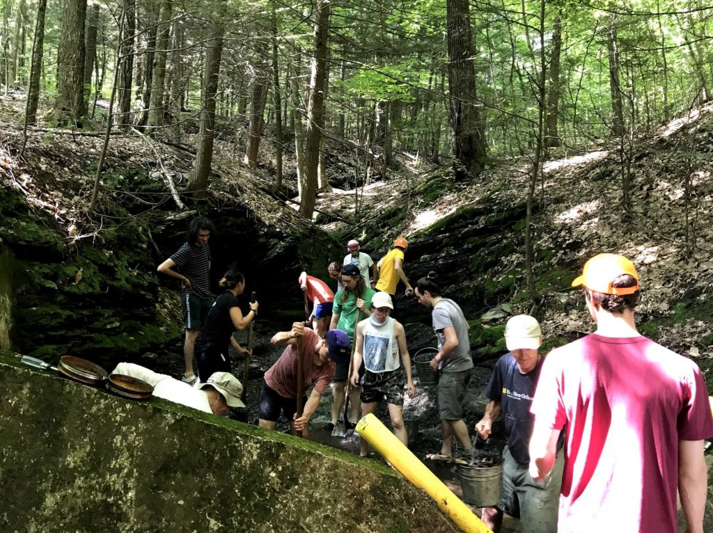 group of 10 people in the woods shoveling sediment